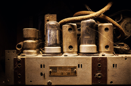 old vintage: Old tubes and electric parts of an old dusty amplifier. Stock Photo