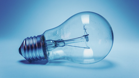 electric bulb: Not so clean unused electric bulb, blue illumination. Stock Photo