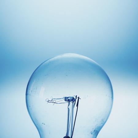 unused: Not so clean unused electric bulb, blue illumination. Stock Photo