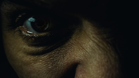 insane: Part of a male face, details of an angry eye, dark atmosphere. Stock Photo