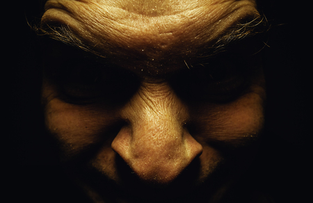insane insanity: Facial expression of an ugly male face, details of eyes in dark and wrinkled skin.