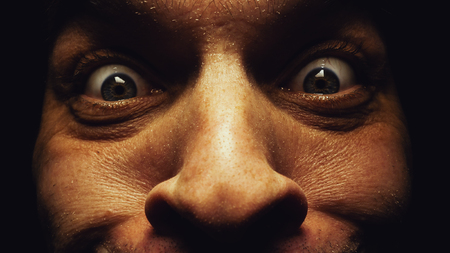 insane insanity: Surprised eyes of a male face, dark atmosphere, details and closeup view on eyes and skin.