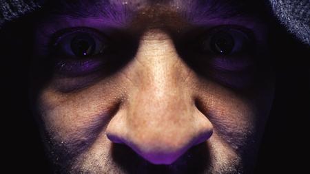human eye: Mens eyes in dark ambient, person with hood looking surprised.