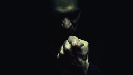 behaving: Dark person showing the fist. Man full of hate and evil eyes. Stock Photo