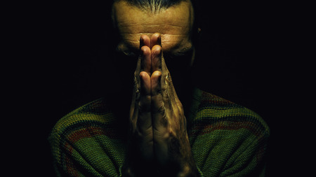 coupled: Man is praying, dark ambient, coupled hands and dark face.