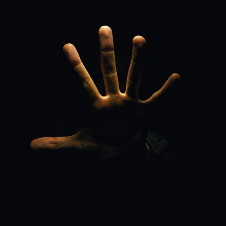 behaving: Just an open hand, and two mans eyes can be seen in the dark. Stock Photo