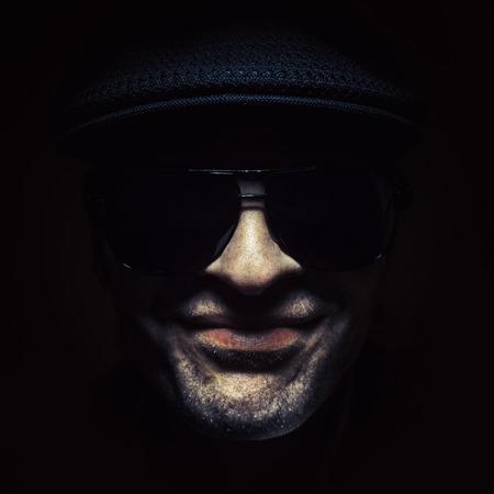 hombre con sombrero: Hombre fresco en buen estado de ánimo, con un sombrero y gafas de sol.