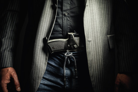 man holding gun: Details of a man with pistol, conceptual composition about having a gun.