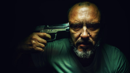 tendencies: Portrait of a hard depressed man, holding a pistol on his forehead.