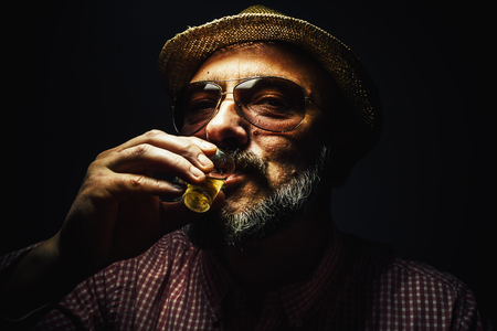 unique characteristics: Happy middle age man drinking an alcoholic drink.