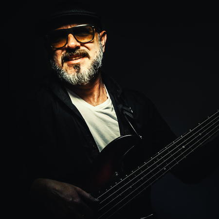 dramatic characters: Portrait of an older musician playing bass with five strings.