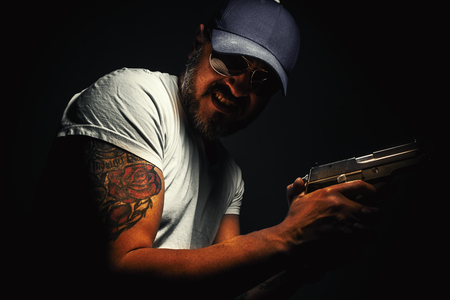 dramatic characters: Facial expression of a man with tattoo and gun.