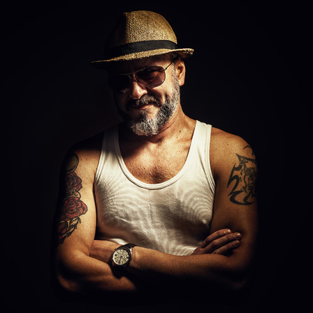 middle age: Portrait of an older man showing his tattoo. Stock Photo