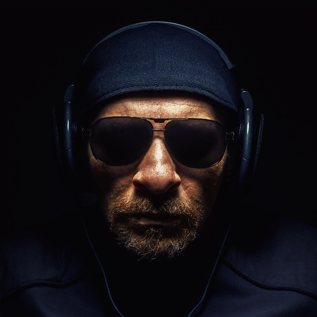 exemplary: Portrait of a man wearing a headphones, strong face and beard details.