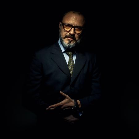 Portrait of an older businessman, showing something.