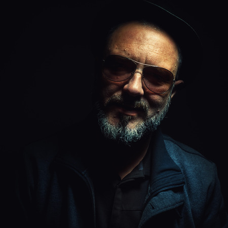 middle age man: Portrait of a modern middle age man, wearing black clothes, hat and sun glasses. Stock Photo