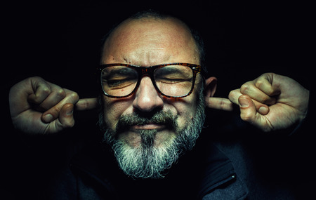 dramatic characters: Portrait of an older man, wearing glasses, with fingers in ears, eyes closed tight. Stock Photo