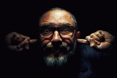 eyes wide: Portrait of an older man, wearing glasses, with fingers in ears, eyes wide opened.