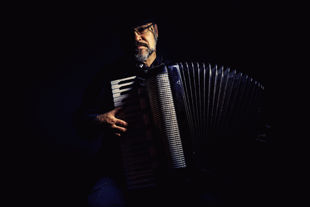 playing music: Portrait of an accordion player, playing and posing. Stock Photo