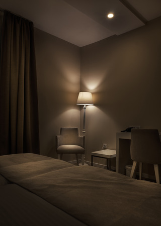 ambience: Details of a hotel room, retro lamp and armchair, big dark brown curtains, calm ambience during night.