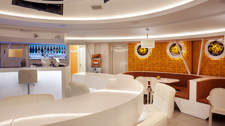 Interior of a modern cafe bar, white futuristic furniture with interesting lighting.