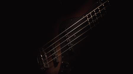 Details van een elektrische basgitaar met vijf snaren.