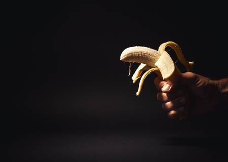 symbolically: Conceptual composition, male hand holding a banana as gun, symbolically representing a caution about healthy diet, or it is better to hold a food than a gun, etc.