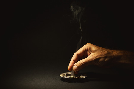 extinguish: Conceptual composition about quit smoking, mans hand extinguishes a cigar. Stock Photo