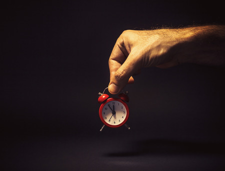 symbolically: Conceptual composition, mans hand holding a red souvenir clock, time is five to twelve, it is about the time or is it too late. Stock Photo