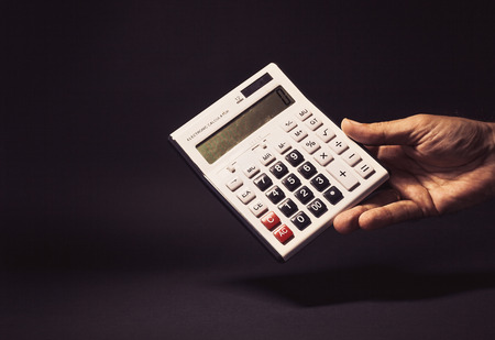 symbolically: Conceptual composition, mans hand holding an old electronic calculator with zero on it.