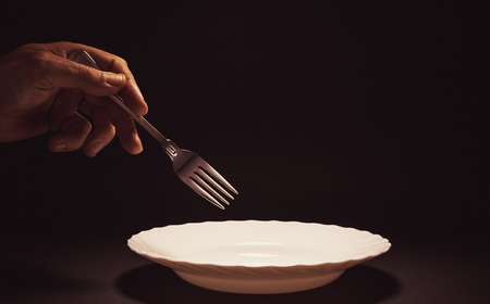 Conceptual composition, mans hand holding a metal fork over an empty plate, issue about food, poverty, etc. Stock Photo