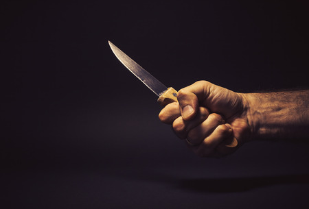 symbolically: Conceptual composition, mans hand holding a big kitchen knife, as self defense   weapon or some kind of horror scene. Stock Photo
