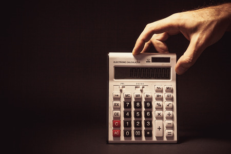 billion: Conceptual composition, mans hand holding an old electronic calculator with billion on it. Stock Photo