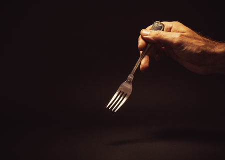 Conceptual composition, mans hand holding a metal fork on empty background.