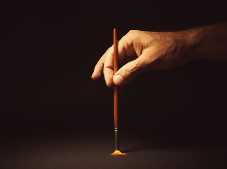 symbolically: Conceptual composition, mans hand holding a brush on black background. Stock Photo