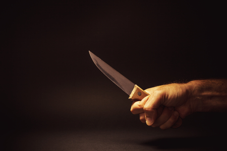 offensive: Conceptual composition of a dangerous situation, somebody is holding a knife.