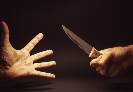 holding a knife: Conceptual composition of a dangerous situation, somebody is holding a knife.
