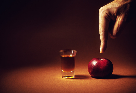 Conceptual composition about choosing healthy life, male hand pointing to apple instead of glass of alcoholic drink. Stock Photo