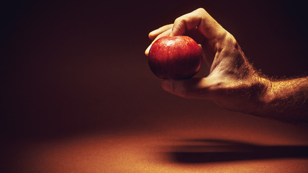 Conceptual composition about choosing healthy life, male hand holding an apple.