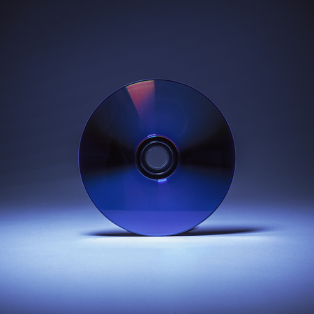 compact disk: Simple composition, closeup view of a compact disk in blue background.