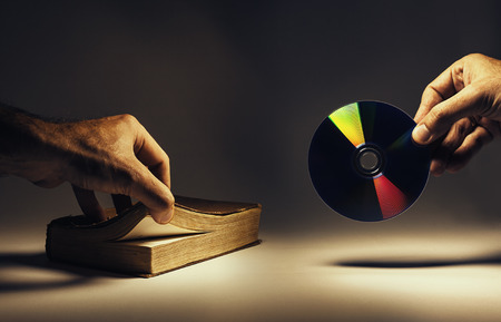 data archiving: Conceptual composition about archiving data, old way as a book and new as a CD.