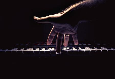 Playing a keyboard, one male hand playing, accentuated contrasts.