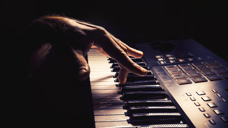 Playing a keyboard, left hand act, accentuated contrasts. Stock Photo