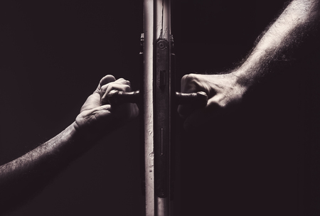 stranger: Conceptual composition about bad relationships, male hands on different sides of a door.