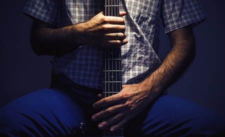 instrumentalist: Hands of a bass player, closeup view on an instrument and body.