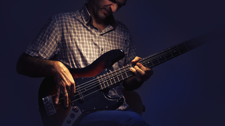 instrumentalist: Bass player and his guitar, expressions while playing.
