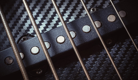 frets: Closeup view on details of strings of jazz bass guitar.