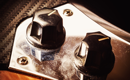 Closeup view on knobs for volume and tone control of a jazz bass guitar.