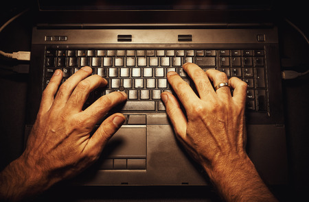 two hands: Conceptual composition about using modern technologies, laptop and male hands. Stock Photo