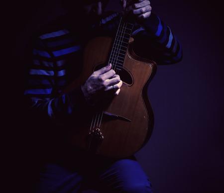 gitana: El músico y su guitarra gitana en un ambiente de color azul oscuro.